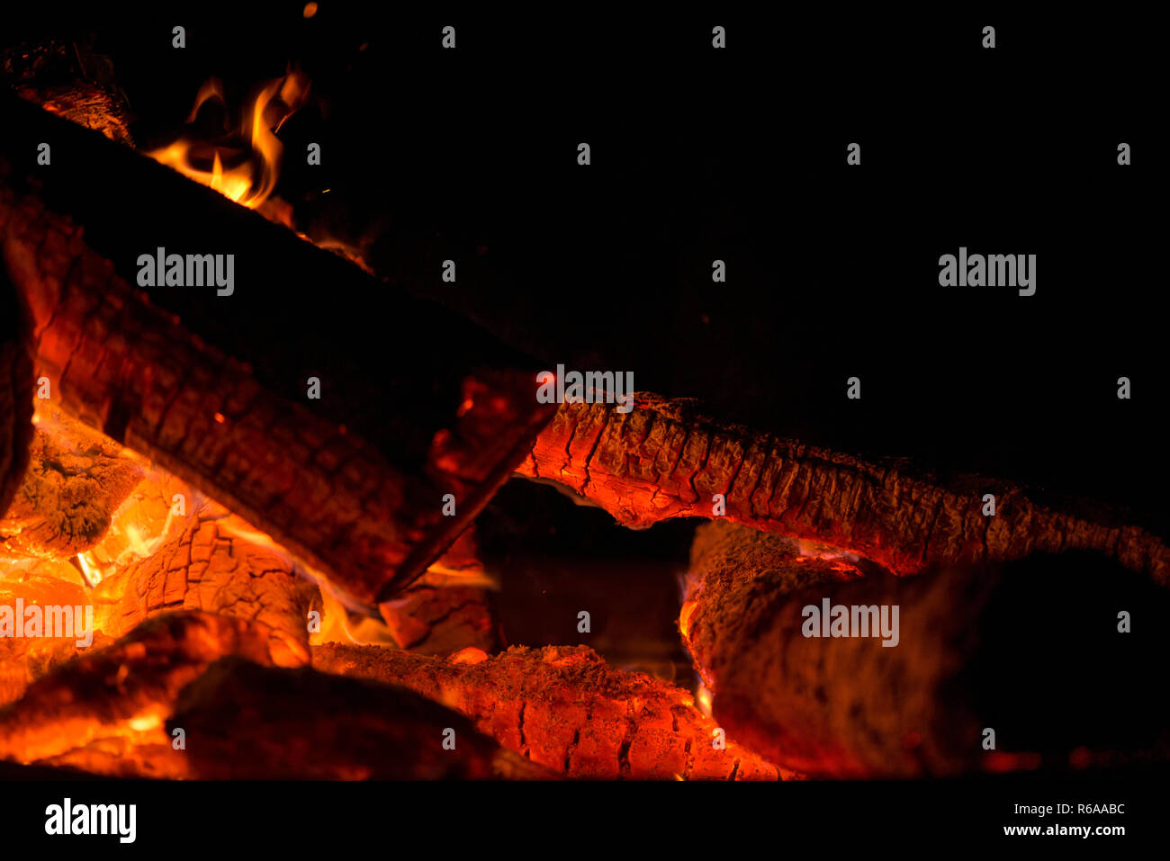 Ignite the fire. Warming up the cold winter nights. A macro shot of firewood, white dust and hot, glowing coal. Burning branches and wood. Flames in t - Stock Image
