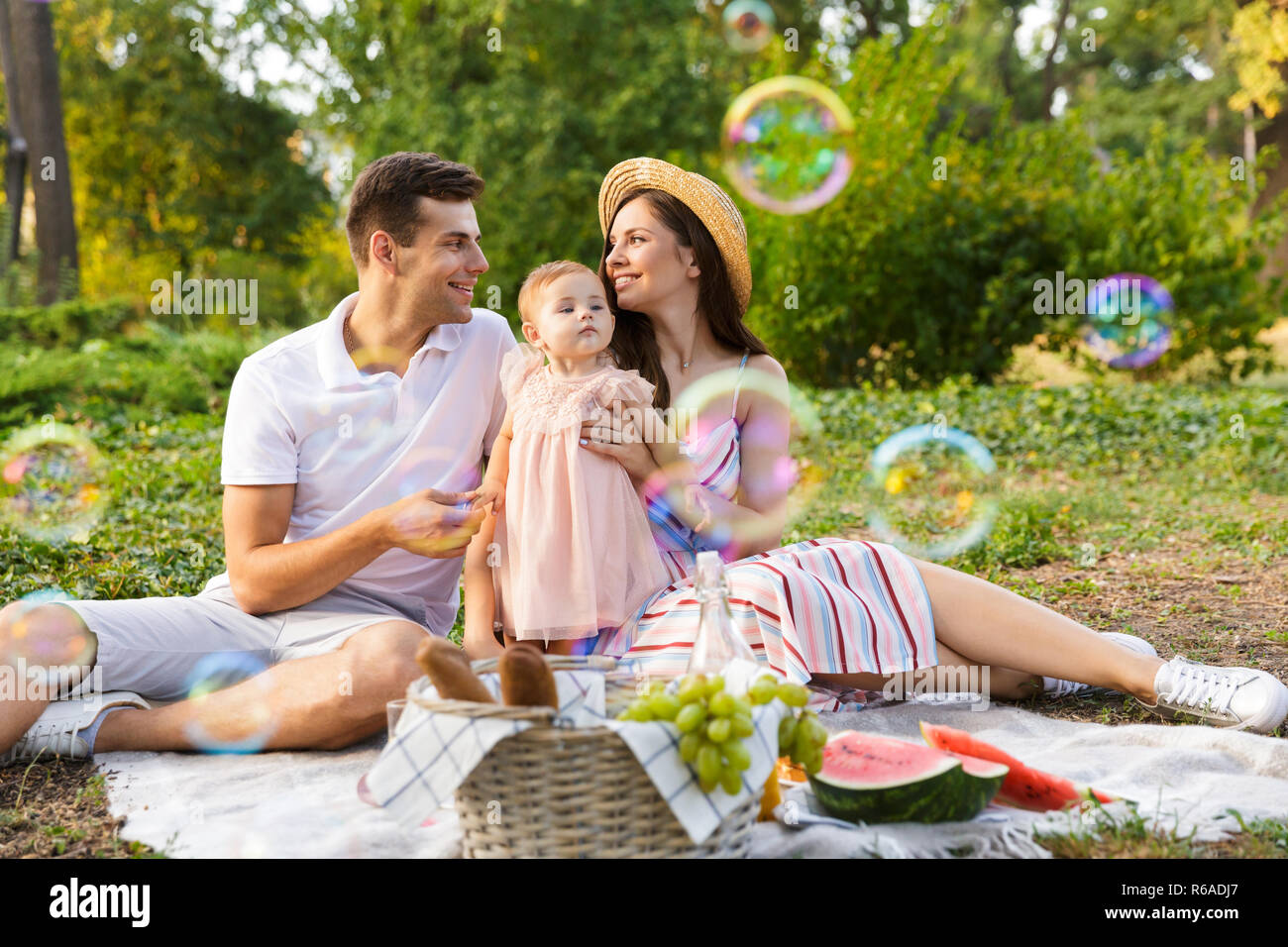 Positive young family with little baby girl spending time together at the park having a picnic
