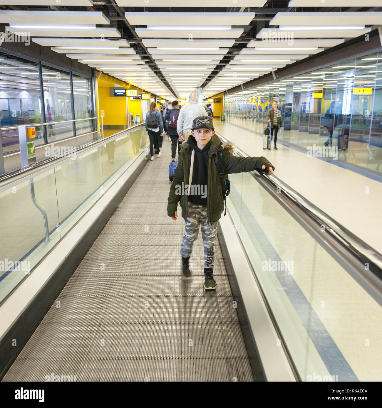 Nine year old boy on a moving walkway at  London Gatwick Airport  LGW ,England, United Kingdom. - Stock Image