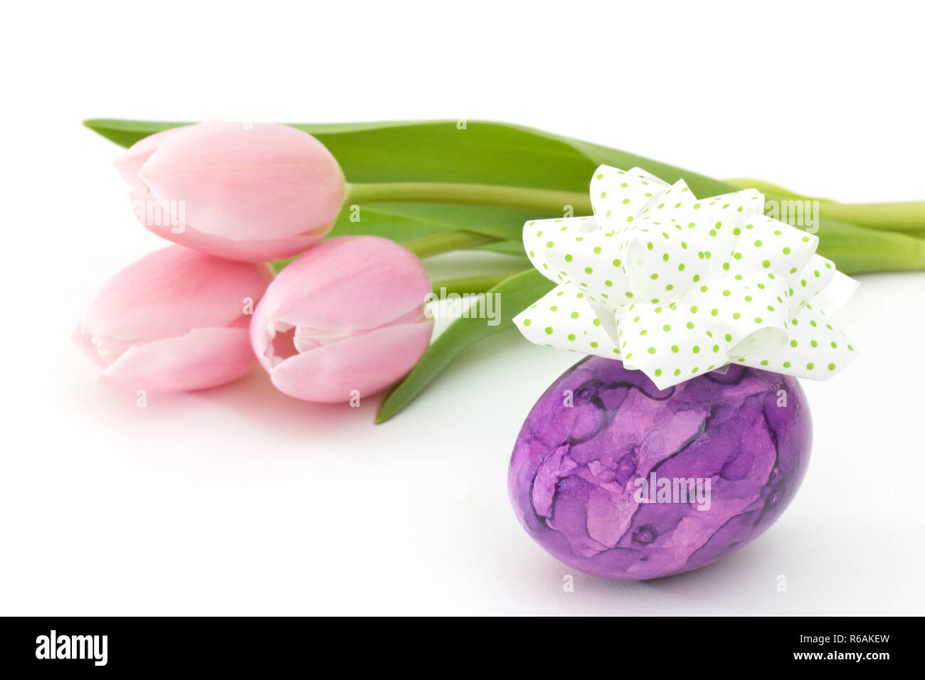 Purple Easter Egg With Bow Near Pink Tulips On White Background Stock Photo