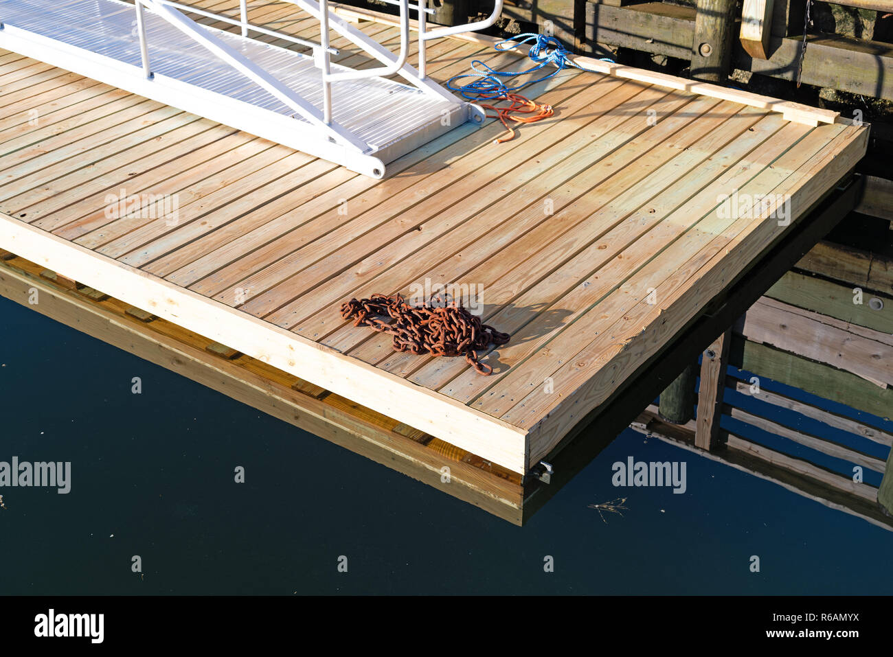 Newly build floating pier with an old chain and new metal walkway at Penobscot Bay at Searsport, Maine in the early morning light. - Stock Image