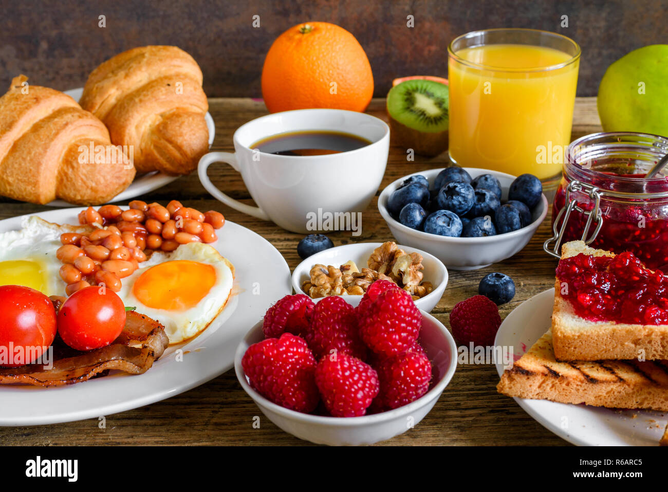 Breakfast including coffee, fried egg ,bacon, beans, croissant, orange juice with nuts, fruits and berries. close up - Stock Image