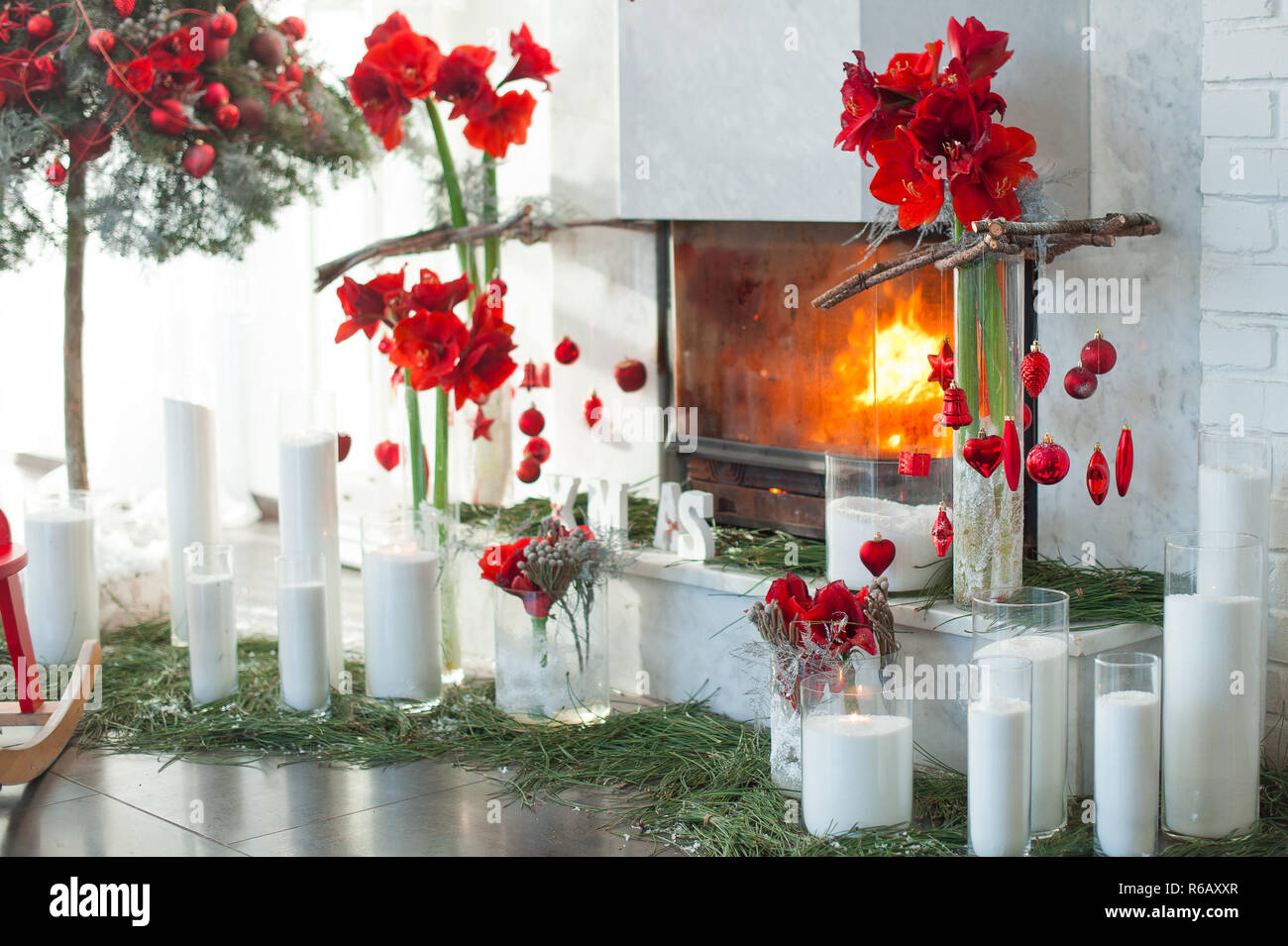 Fireplace Decor With Candles And Red Flowers Stock Photo