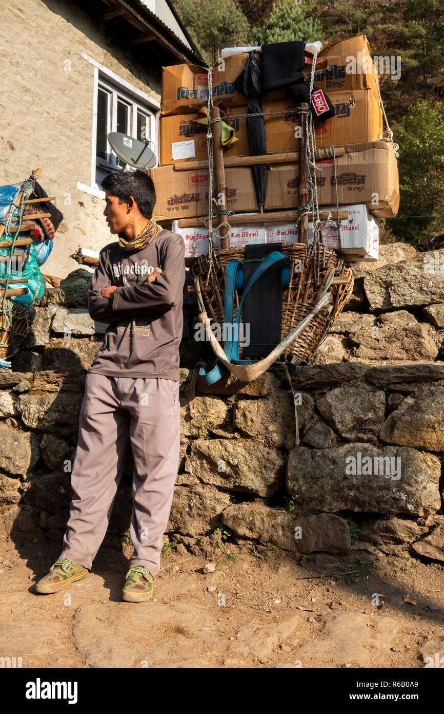 Nepal, Thado Koshi Gaon, young porter resting beside heavy pack on way to Namche Bazaar - Stock Image
