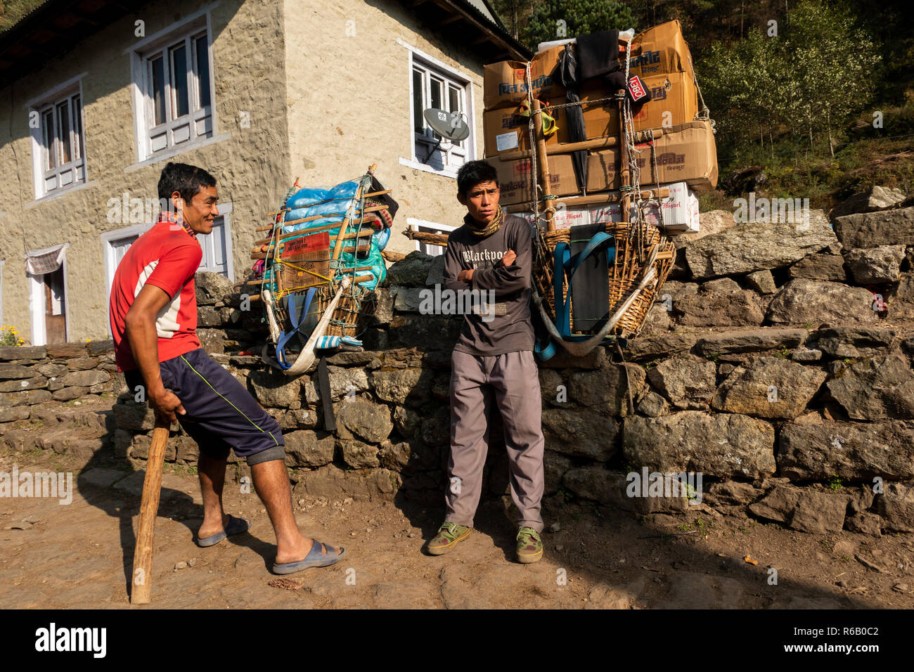 Nepal, Thado Koshi Gaon, young porters resting beside their heavy packs on way to Namche Bazaar - Stock Image