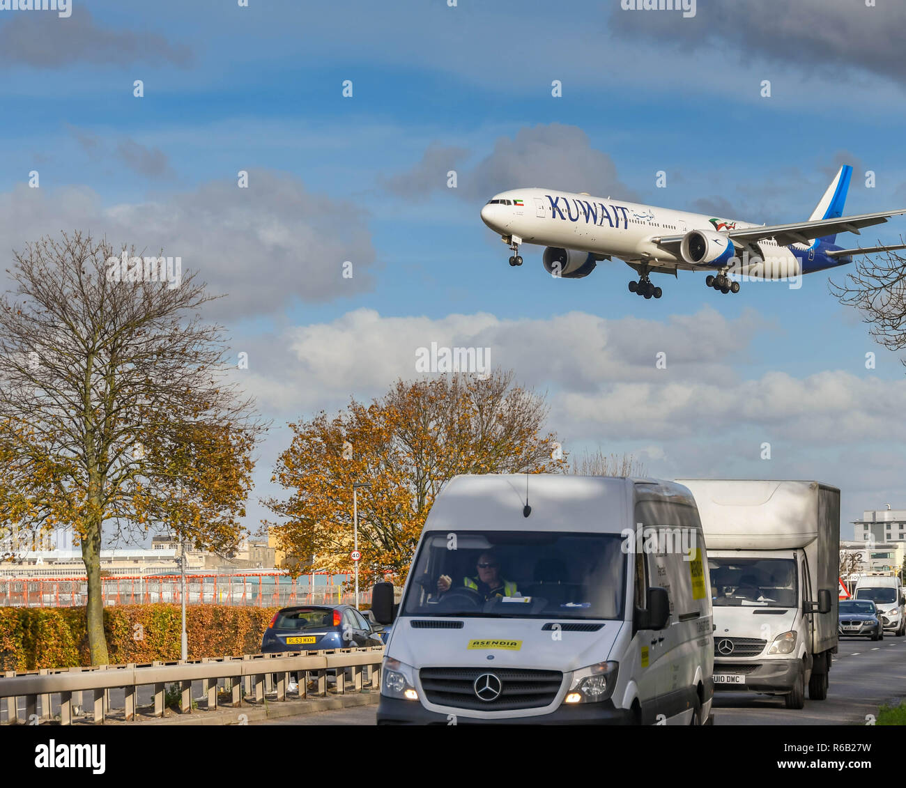 LONDON, ENGLAND - NOVEMBER 2018: Commercial vehicles on the A30 road at London Heathrow Airport with a large passenger jet passing overhead.Stock Photo