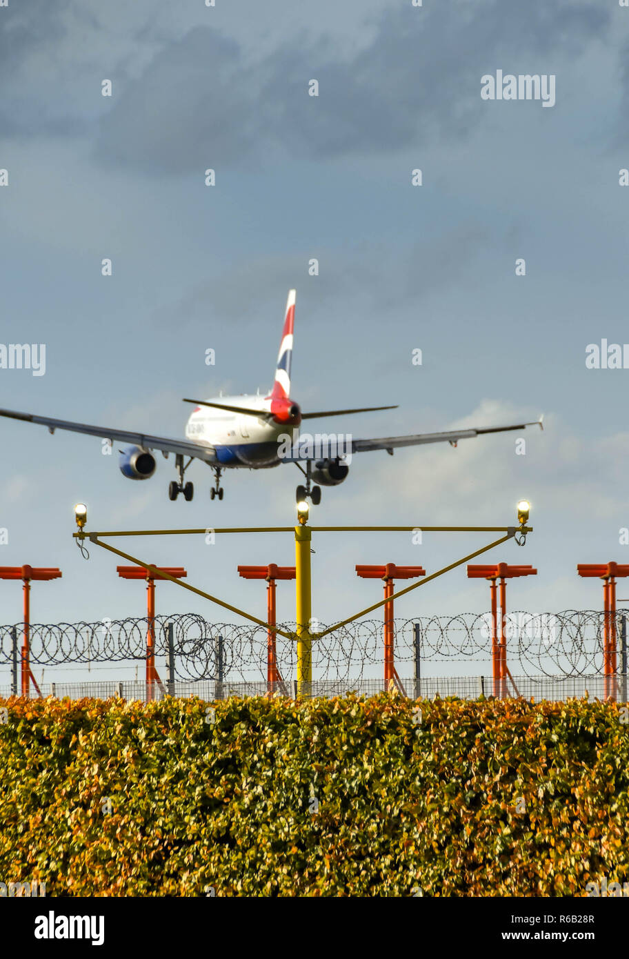 LONDON, ENGLAND - NOVEMBER 2018: Landing lights in front of instrument landling system antennae at London Heathrow Airport. A British Airways jet is a - Stock Image