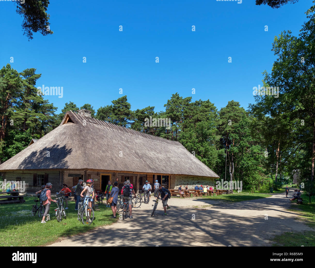 Cyclists outside the 19th century roadside Kolu Inn (from Kolu village in Harju County), Estonian Open Air Museum (Vabaõhumuuseum), Tallinn, Estonia - Stock Image