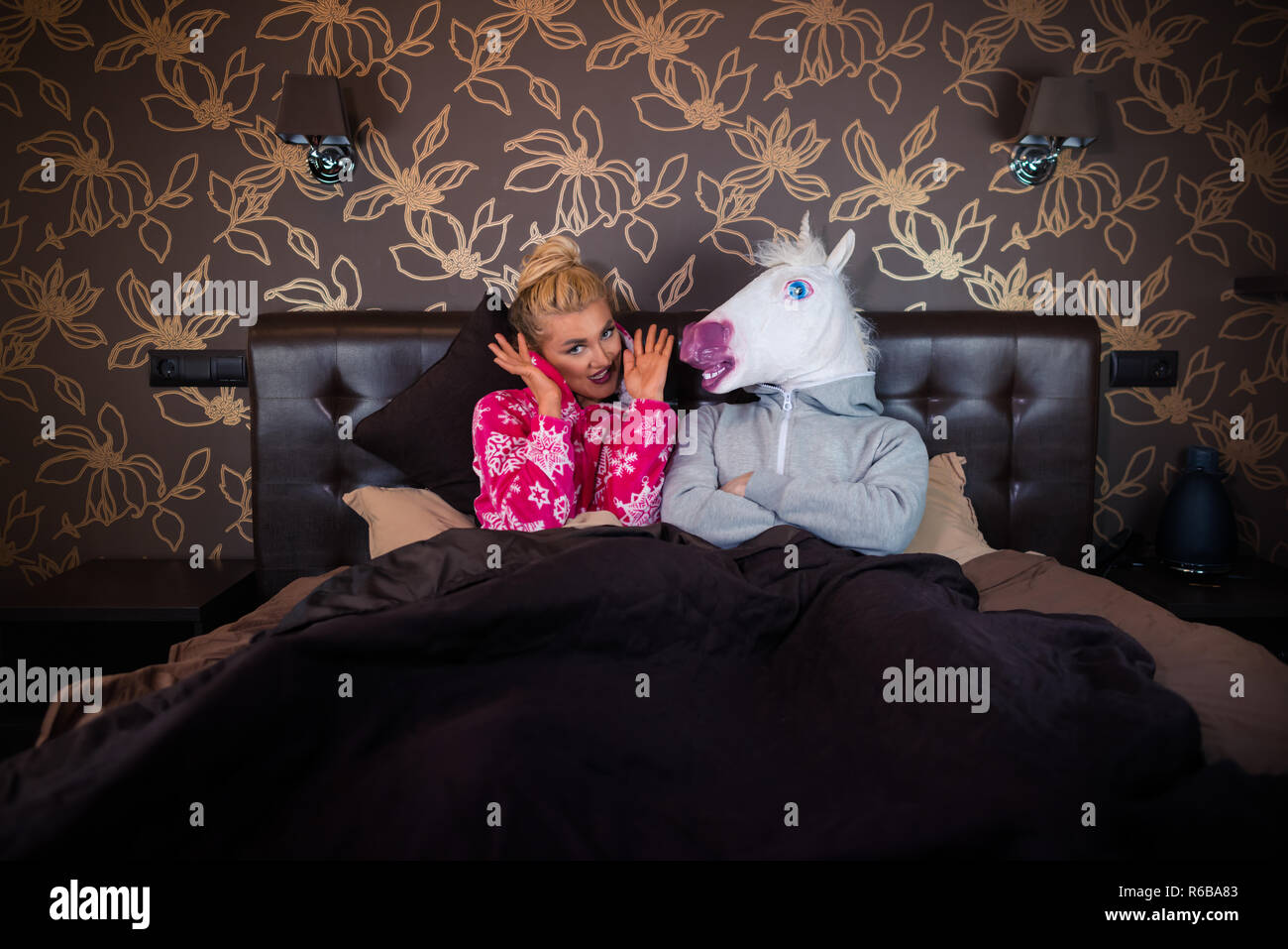 Young woman in pajama sits on the bed with strange boyfriend in unicorn mask. Unusual couple spends time together in stylish apartments. - Stock Image