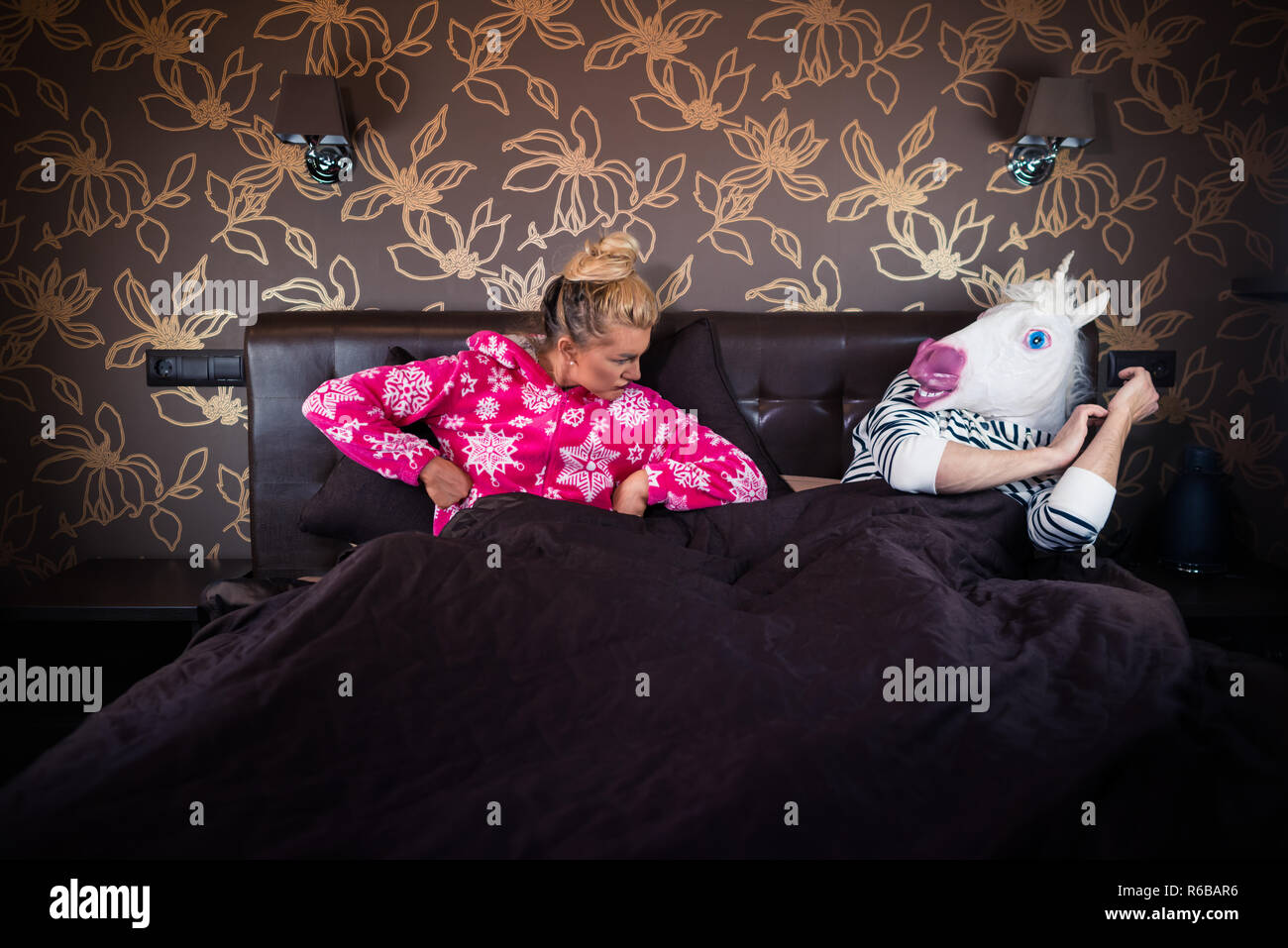 Serious young woman in pajama lying on bed with strange boyfriend in comical mask. Unusual couple has relationship problems at the stylish bedroom. - Stock Image