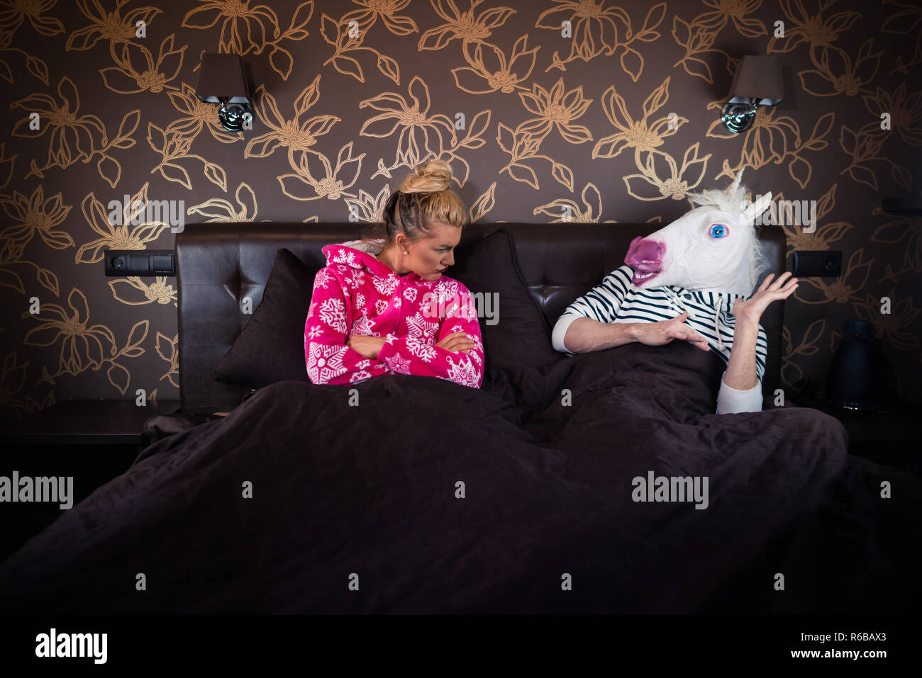 Serious girl in pajama sits on bed with strange boyfriend in freaky mask. Relationship problems of unusual couple. Young woman with unicorn. - Stock Image