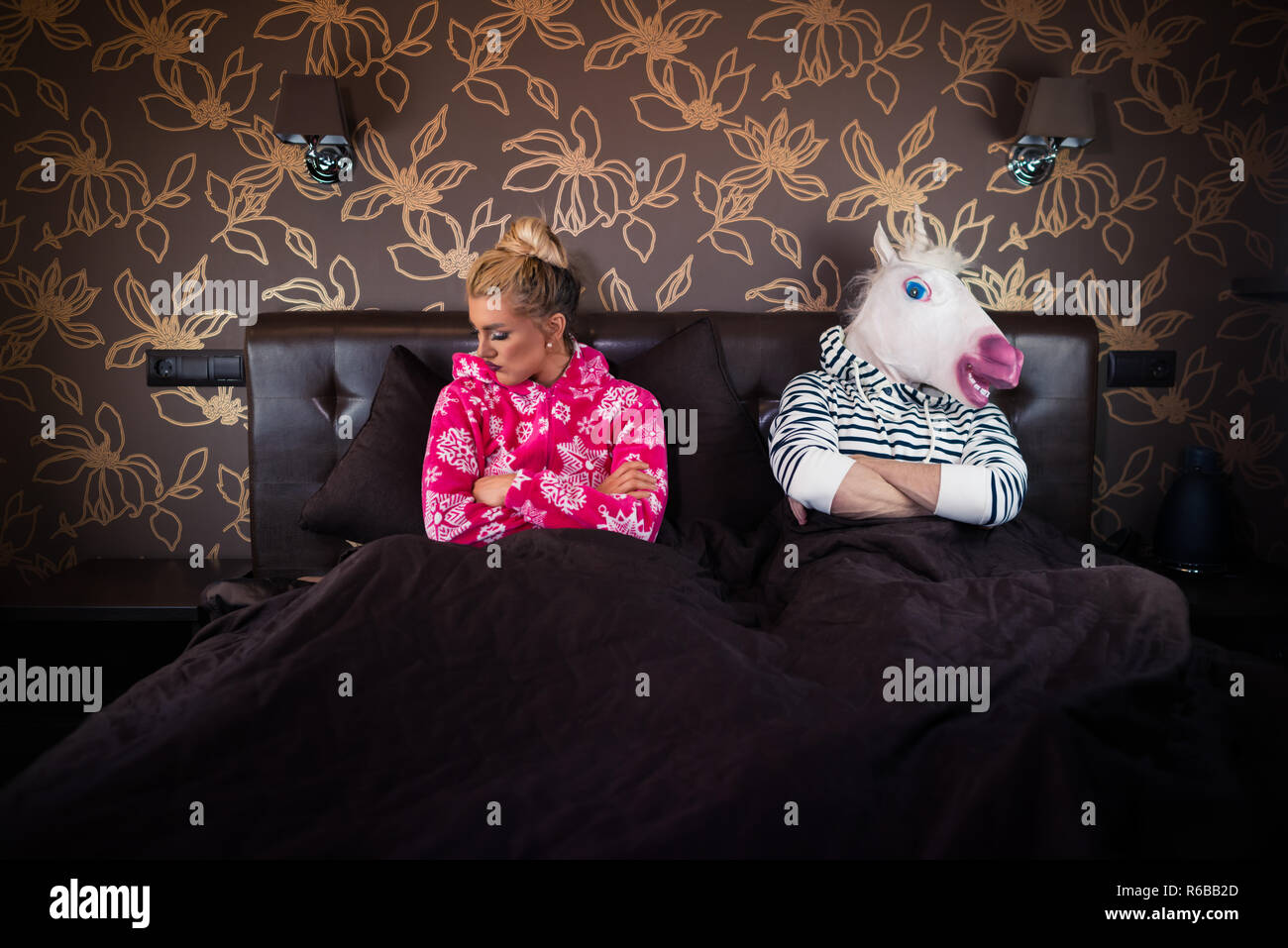 Unusual couple has relationship problems. Beautiful young woman in pajama on the bed with strange boyfriend in freaky mask in stylish apartments. - Stock Image