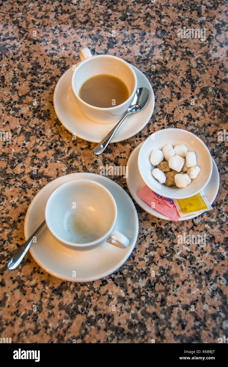 Two white cups of tea on saucers and a sugar bowl with sugar cubes. - Stock Image