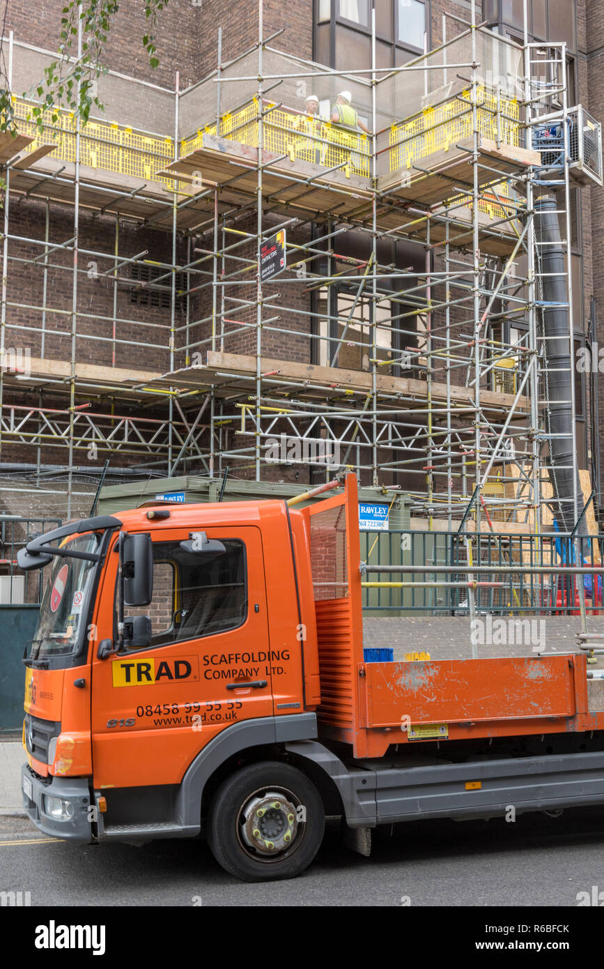 a scaffold on the side of a tall building site with delivery lorry in central London, uk Stock Photo
