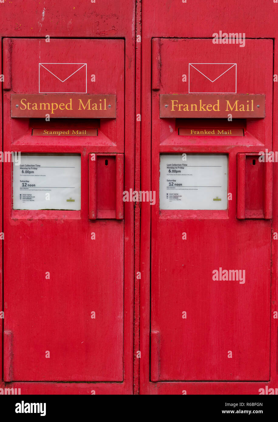 vintage old fashioned royal mail posting boxes set into a wall outside of a post office. - Stock Image
