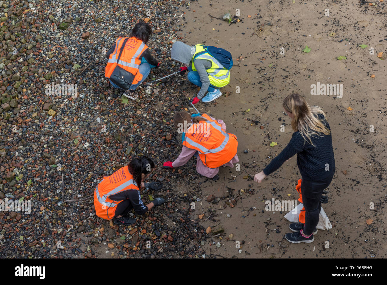 beach cleaners picking up plastic and rubbish from the beach or coast at low tide on the river thames in central london. - Stock Image