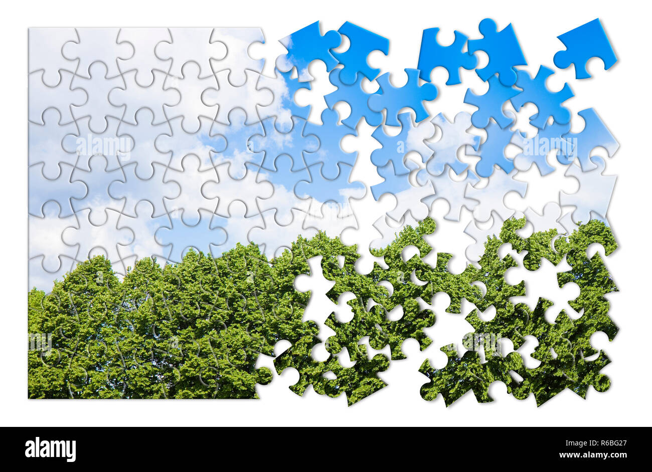 Green trees against a cloudy sky - concept image in puzzle shape - Stock Image