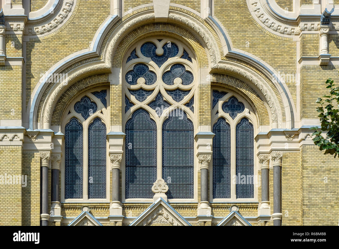 Large arched window of the synagogue with stained glass Windows on the background of the yellow brick wall. - Stock Image