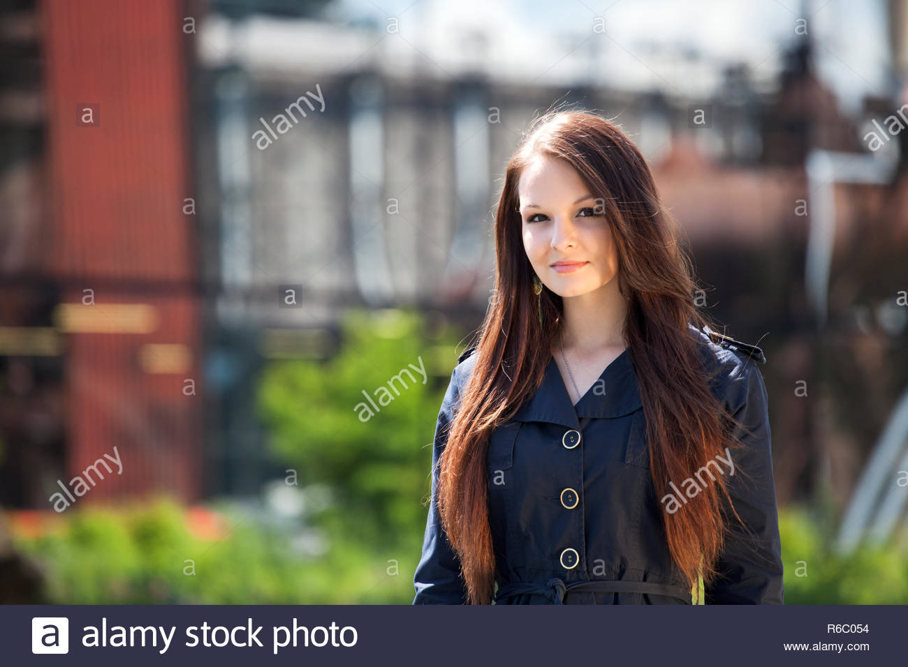 Portrait of young brunette woman in nature, in front of industrial background. - Stock Image