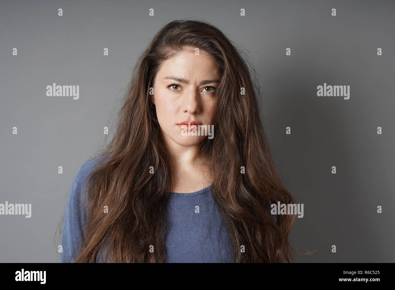 young woman with a serious look on her face - gray background with copy space - Stock Image