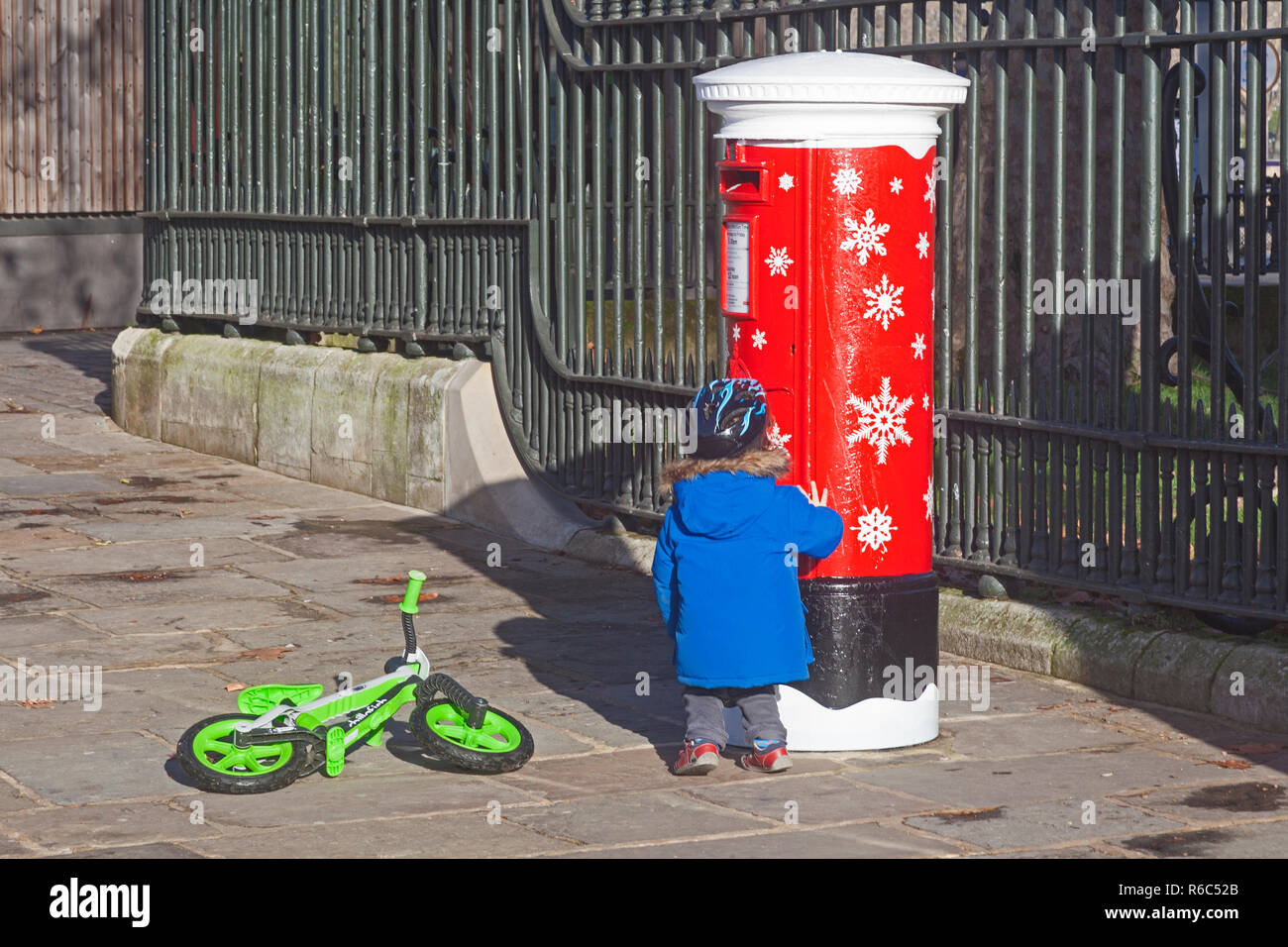 London, Greenwich.  December 2018. A little girl admires a Royal Mail 'singing' musical postbox with its Yuletide decoration. - Stock Image