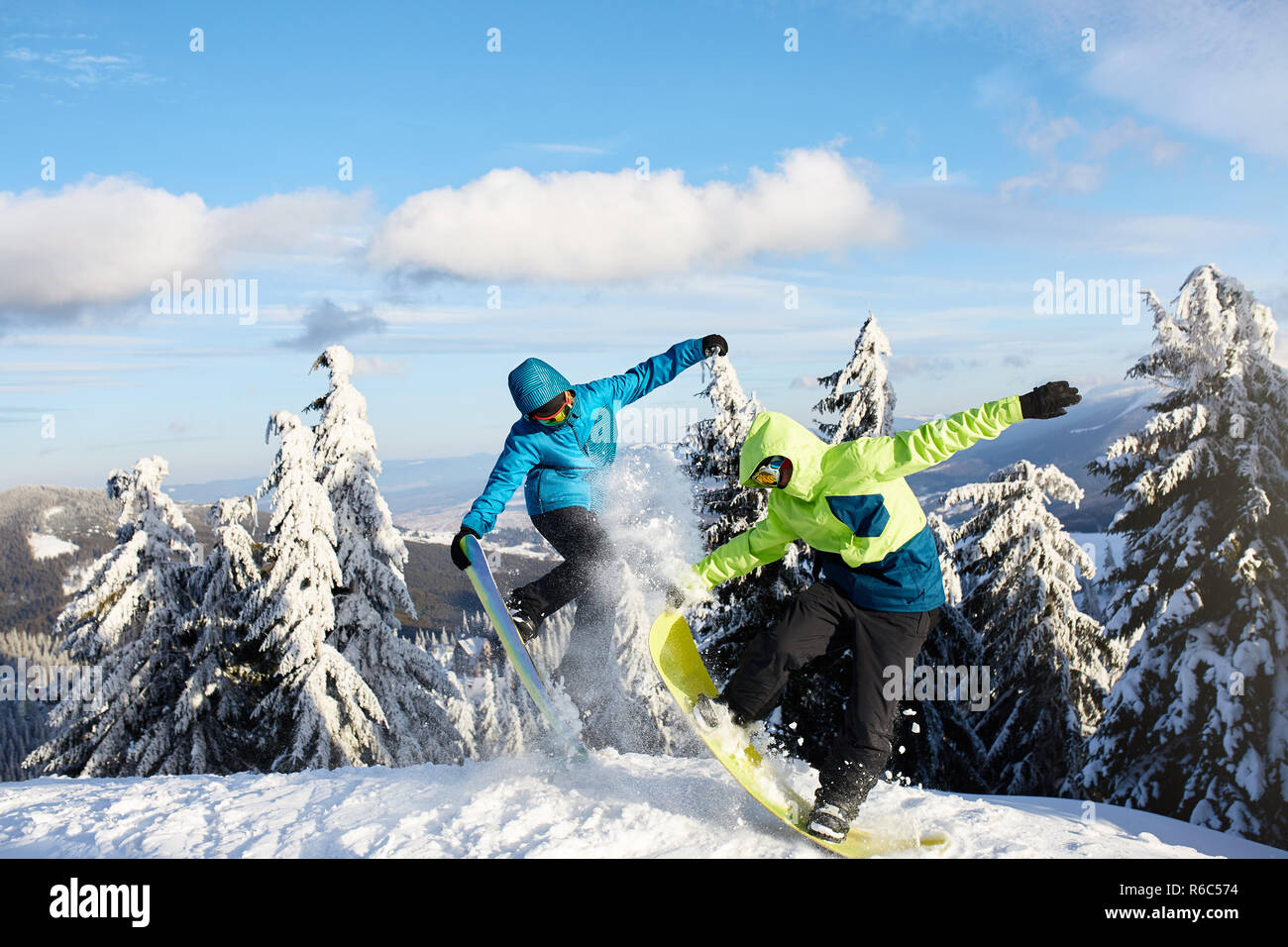 Two snowboarders doing tricks at ski resort. Riders friends performing jump with their snowboards near forest on backcountry freeride session in colorful fashionable outfit. Copyspace area. - Stock Image