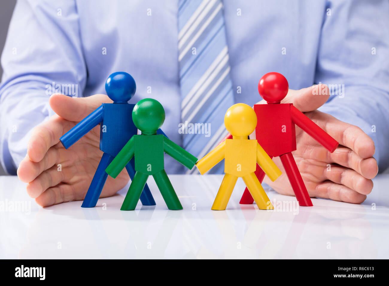 Human Hand Protecting Human Figures Stock Photo