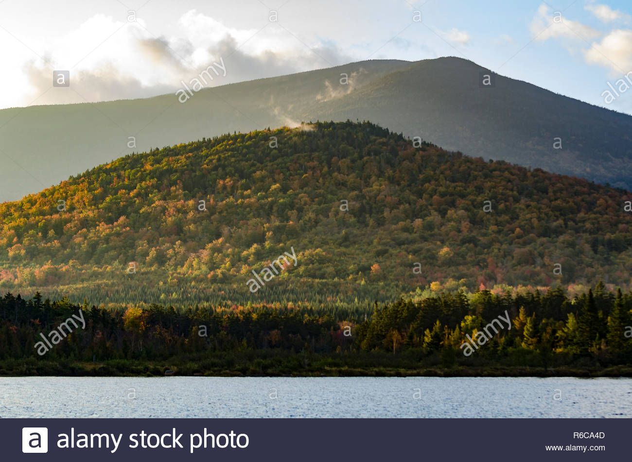 Morning sun lighting fall foliage on hills above pond - Stock Image