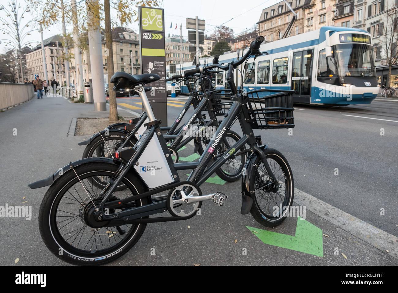 Public Bike bikeshare bikes parked in Zurich, tram in b.g., on Limmatquai. - Stock Image