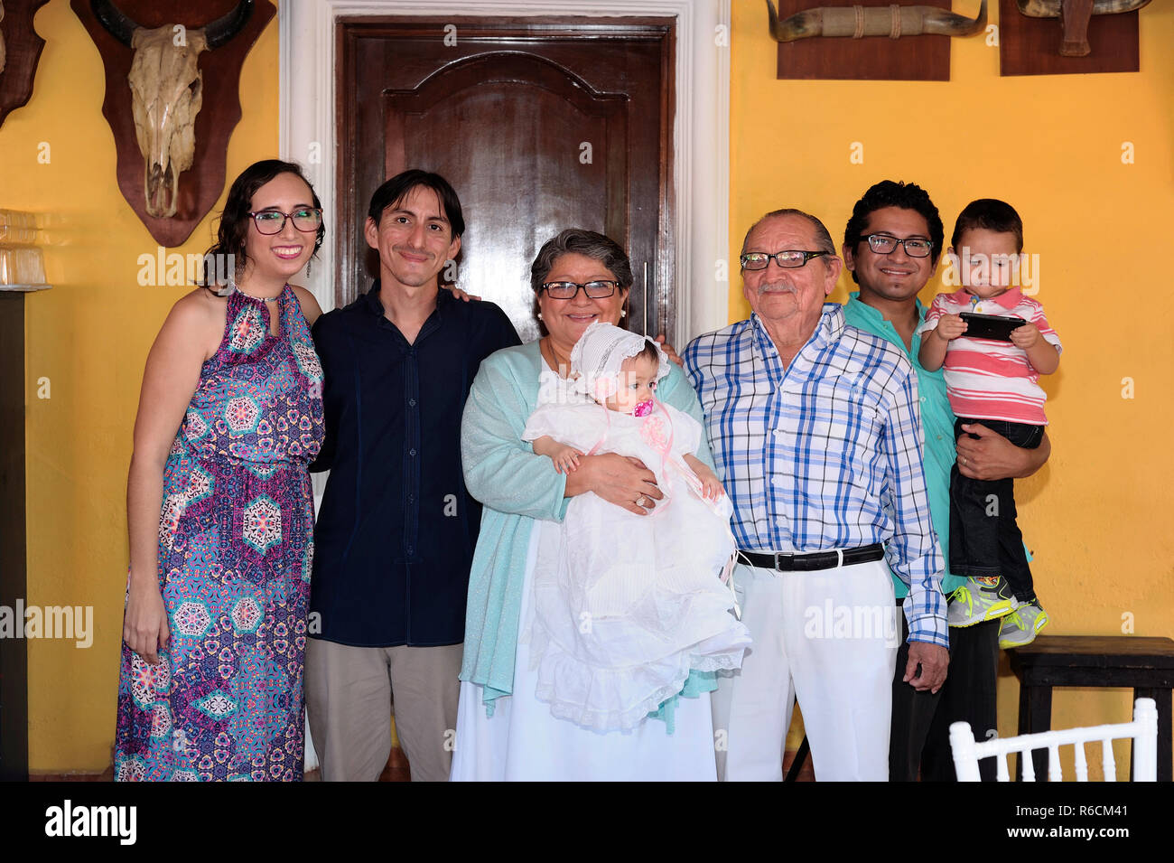 MERIDA, YUC/MEXICO - NOV 13, 2017: Candid portrait of guests holding the just baptised baby girl at the party. - Stock Image