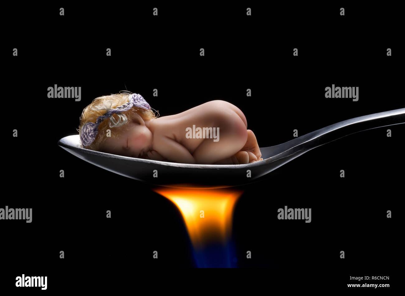 Baby asleep on spoon over burning flame - Stock Image
