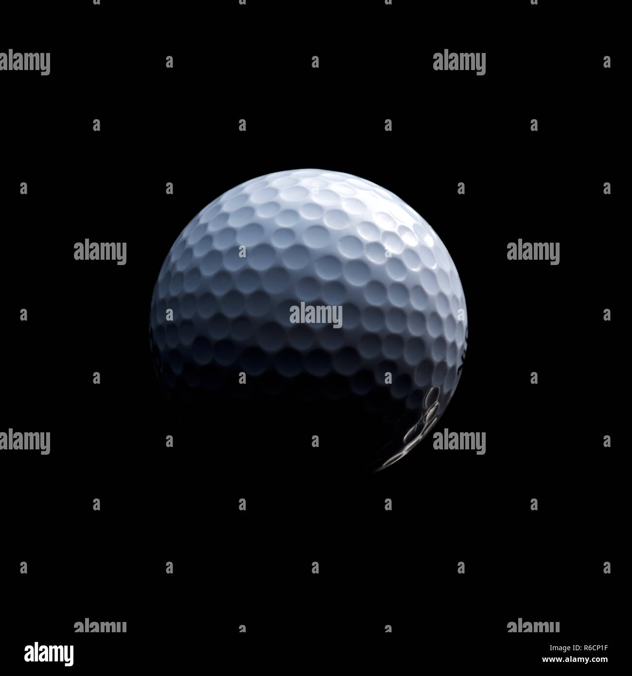 Detailed close of white dimpled golf ball in shadow, black background - Stock Image