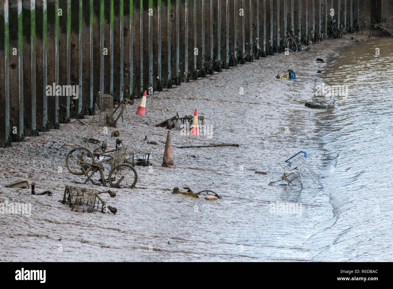 Shopping trolleys, bicycles and other items thrown into a tidal river are being covered over by mud and silt, depicting littering and environment harm - Stock Image