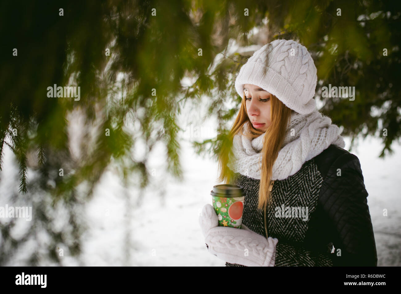 c86131cb9cba94 Portrait of cute woman in white scarf and hat knitted coat on outdoors  background of snow and blurred fir branches in winter. girl holds a coffee  cup in ...