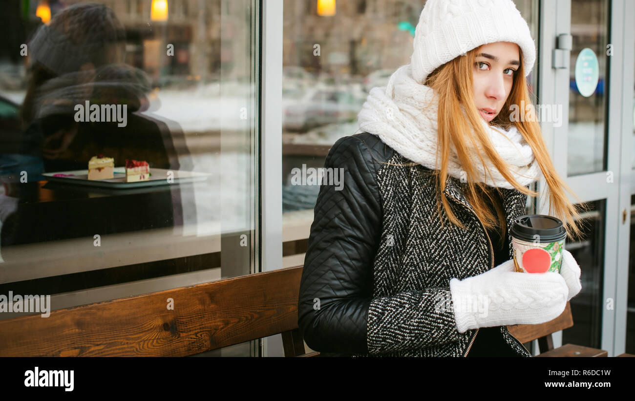 88afd5788a78b6 woman in white scarf and hat drinks coffee. cute young blonde girl sitting  on a bench near the coffee shop, drinking takeaway coffee, holding  Christmas ...