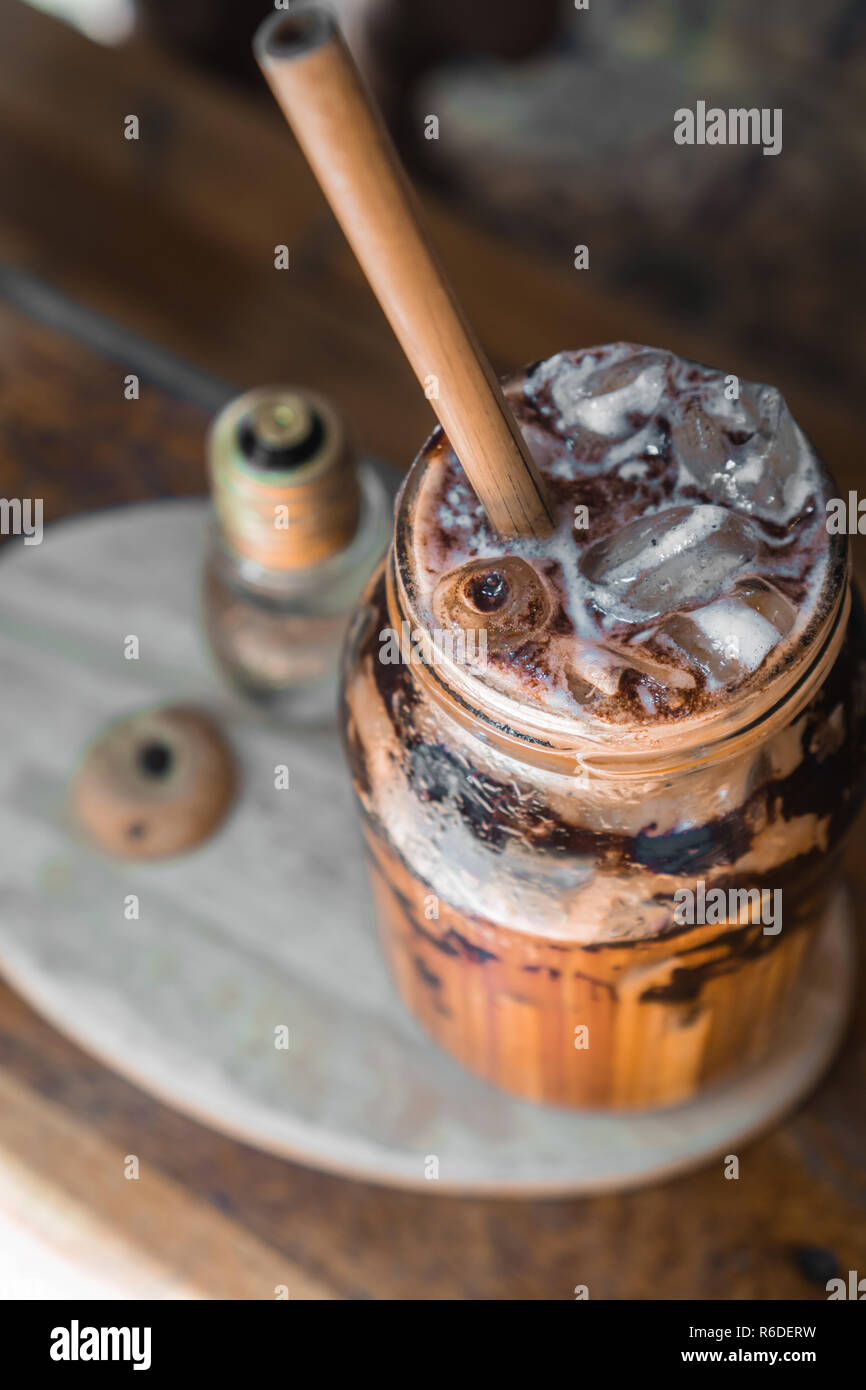 Coffee with a straw on a plate - Stock Image