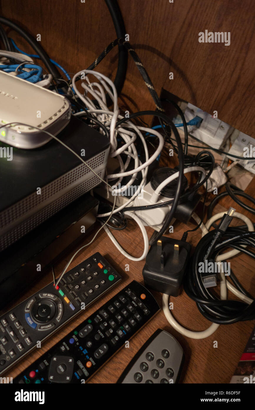 Jumbled wires behind TV control units in a mess at a home in England - Stock Image