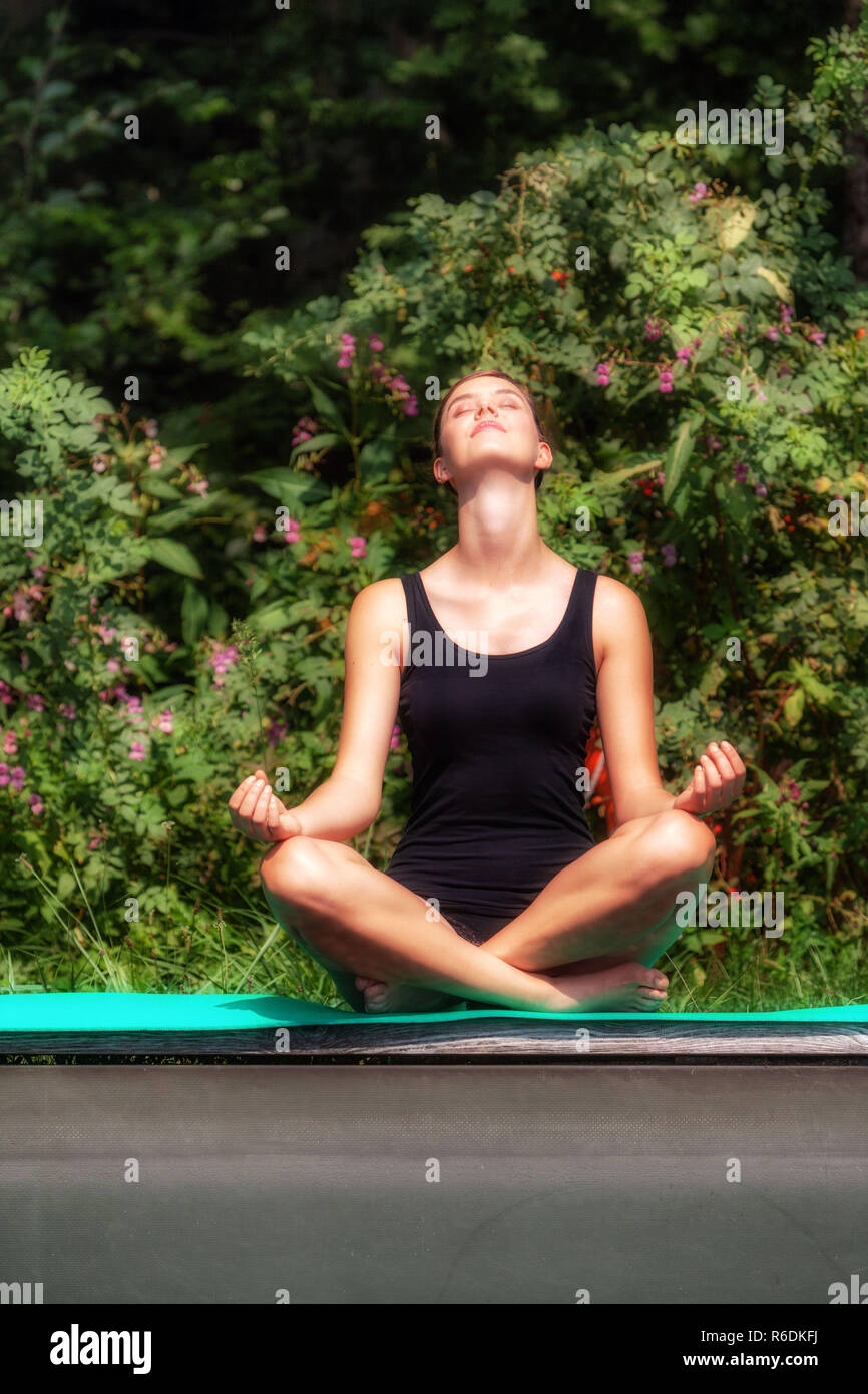 Portrait Of A Young Woman Sitting In Front Of Bushes And Doing Yoga. Stock Photo