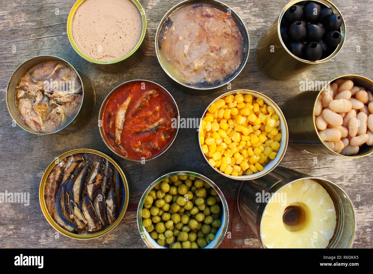 Different open canned food on old wooden background. Top view. Flat lay. - Stock Image