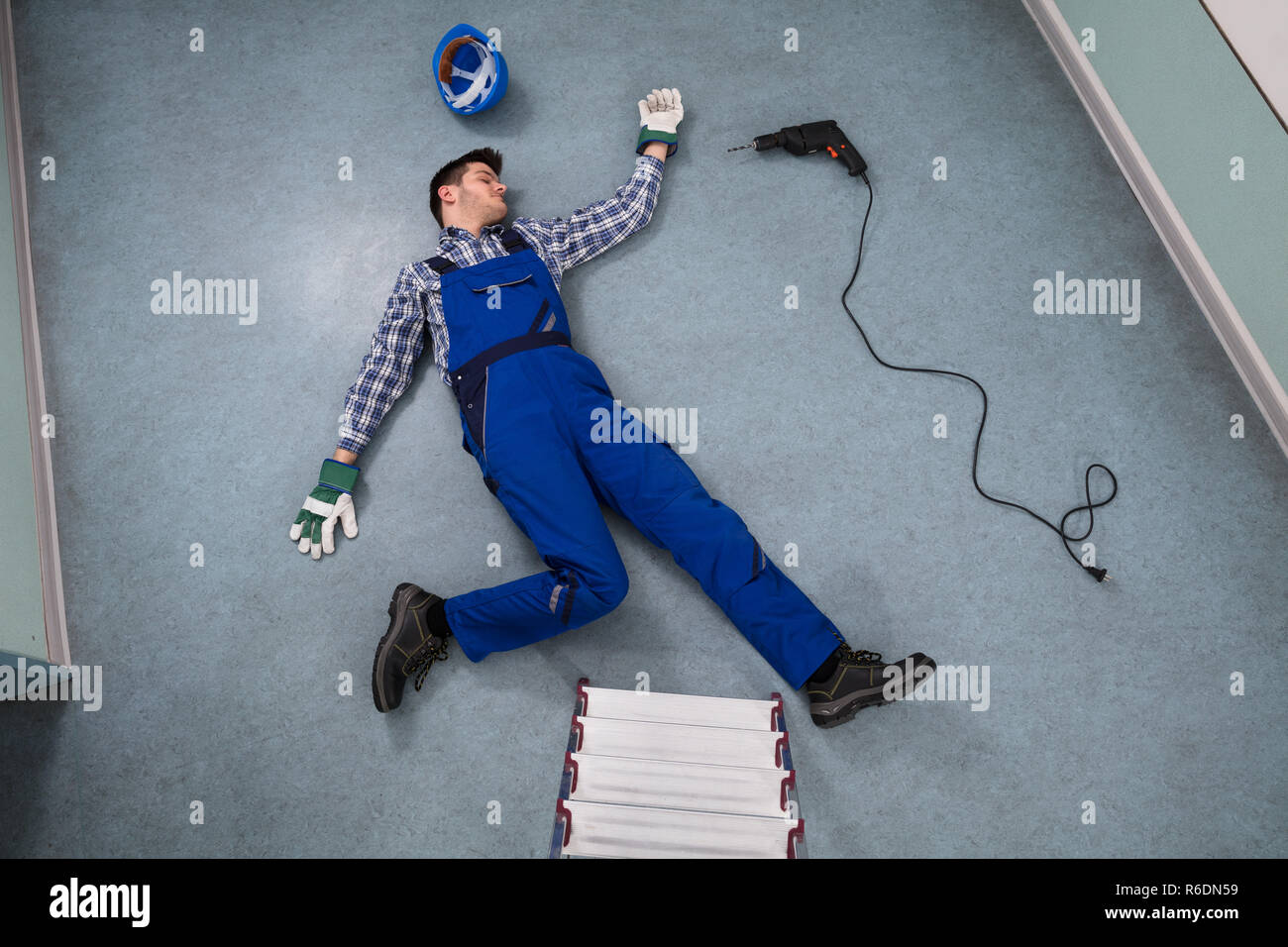 Unconscious Handyman Lying On Floor - Stock Image