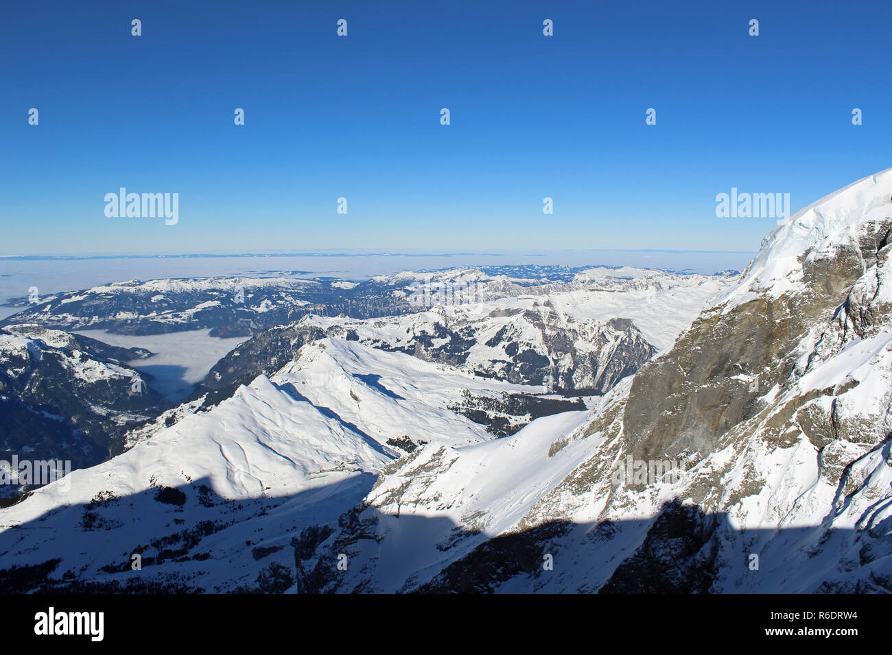 View from Jungfraujoch, Switzerland towards Wengen. Highest railway station in Europe 3,466 m (11,371 ft). Cloudless Sunny Winter day. Stock Photo
