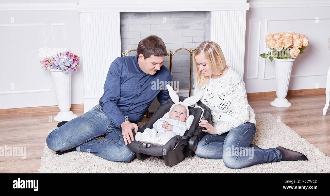 loving parents and a pretty baby in a rabbit costume - Stock Image