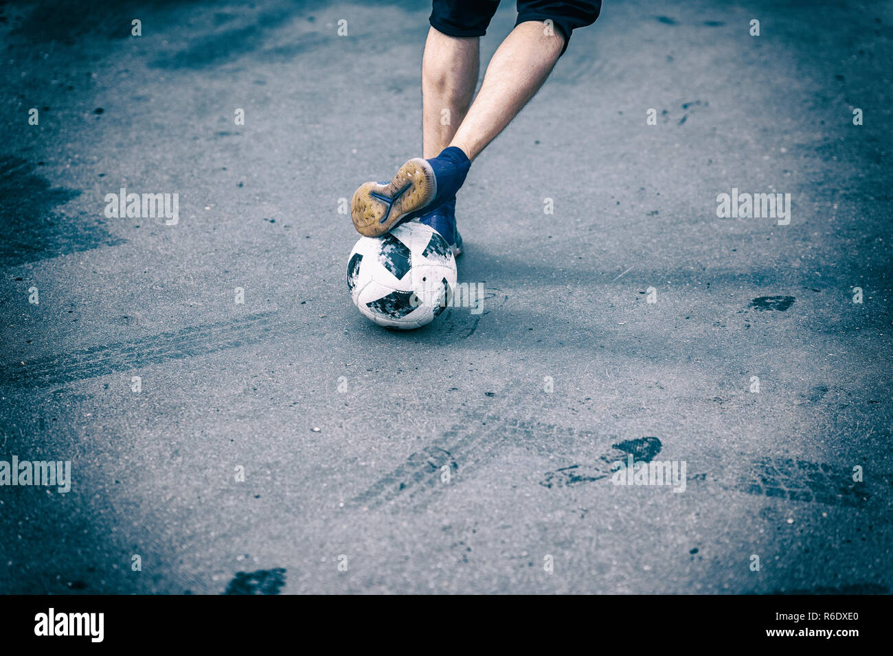 Legs, feet of football player, dribbling with the ball on asphalt in yard - Stock Image