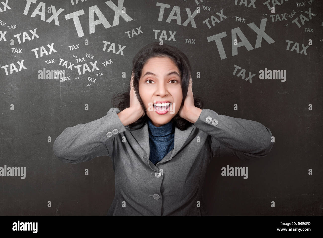 Stressful asian businesswoman with tax sign - Stock Image