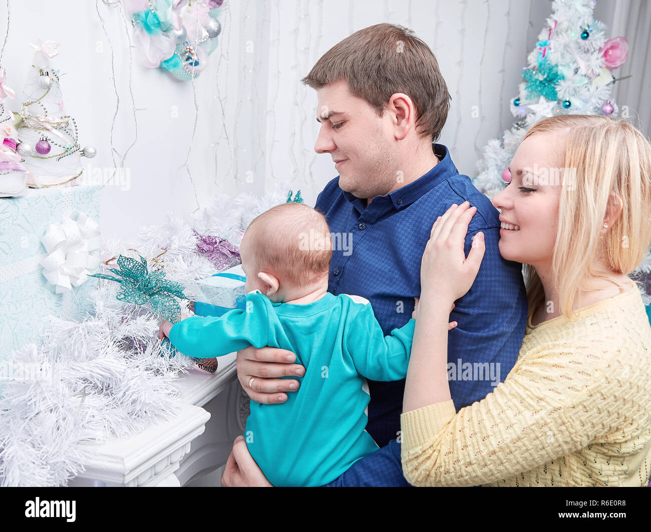 loving parents show their baby Christmas gifts Stock Photo