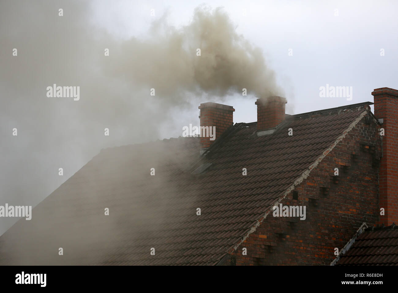 Smoke from the chimney of a house fueled with coal - Stock Image