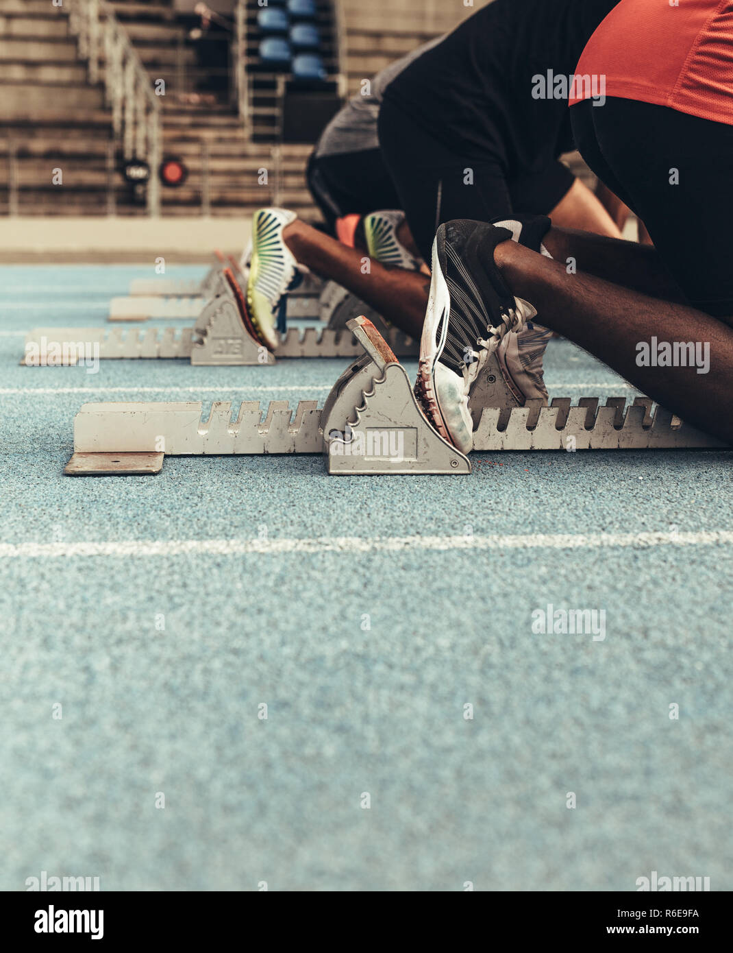 Sprinters on their mark ready to sprint on an all weather running track. Runners using a starting block to start their run on the race track. - Stock Image