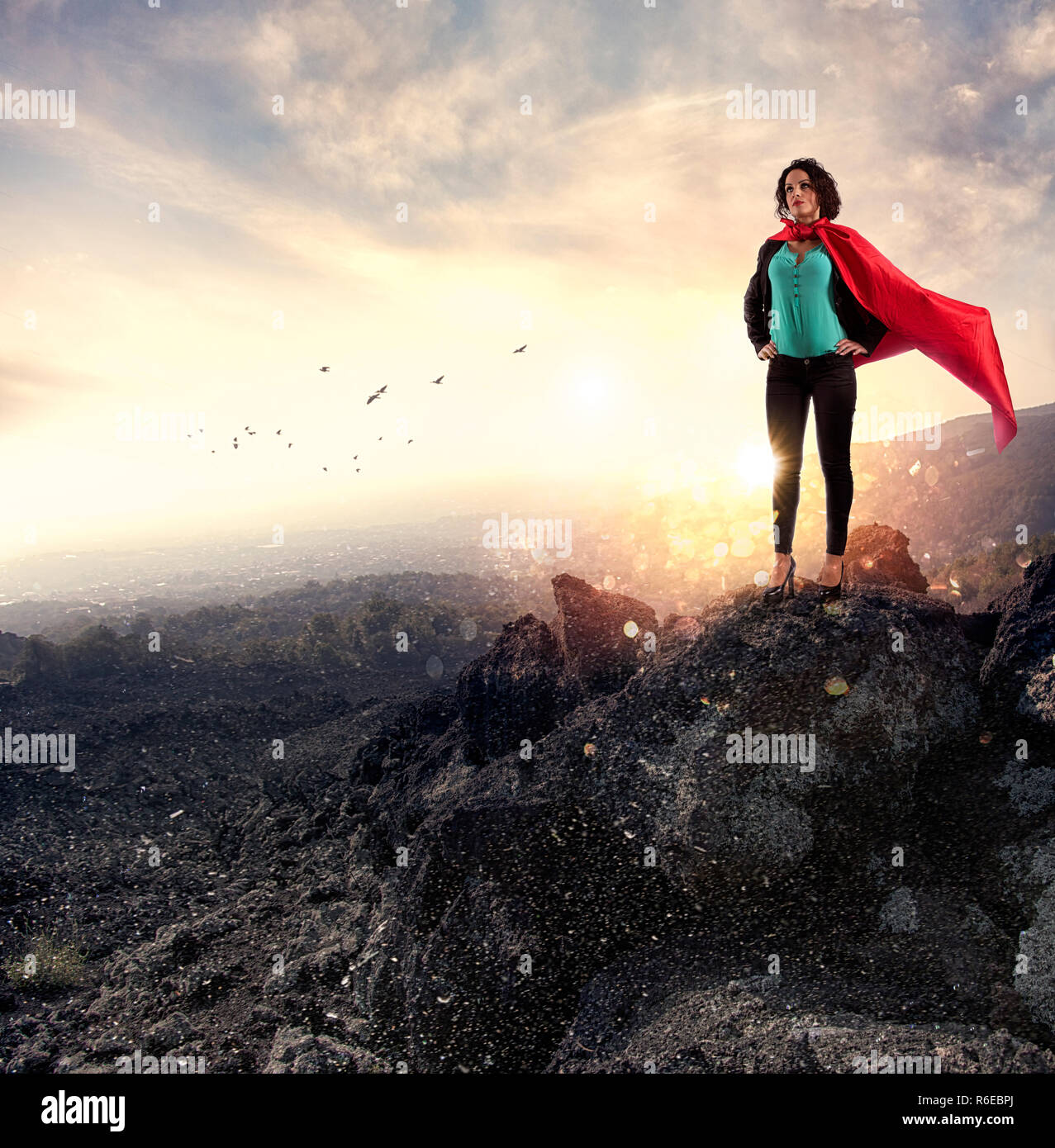 Successful businesswoman acts like a super hero on a mountain. Concept of determination and success Stock Photo
