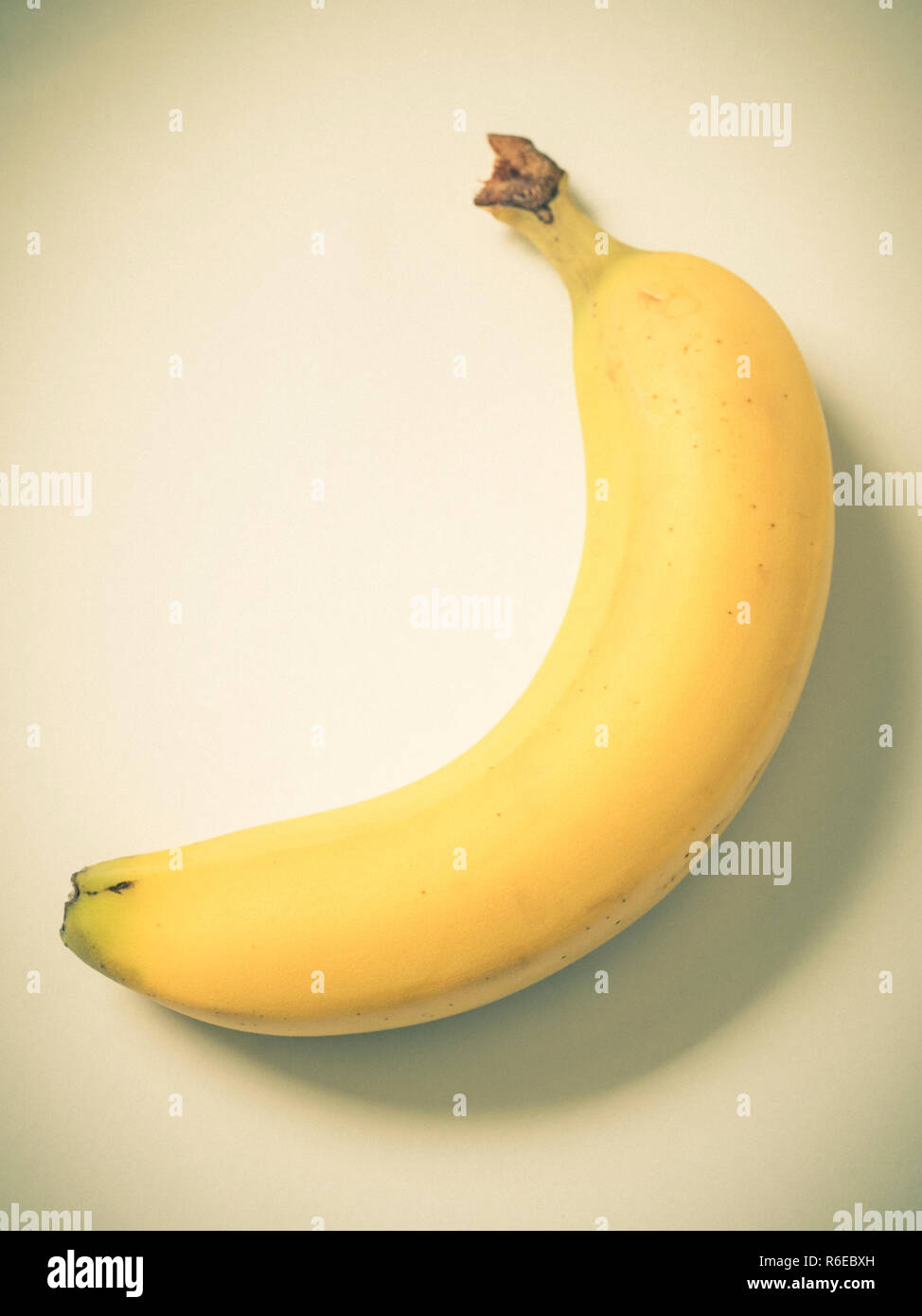 Close up of banana on plate with vignette and desaturated colour - Stock Image
