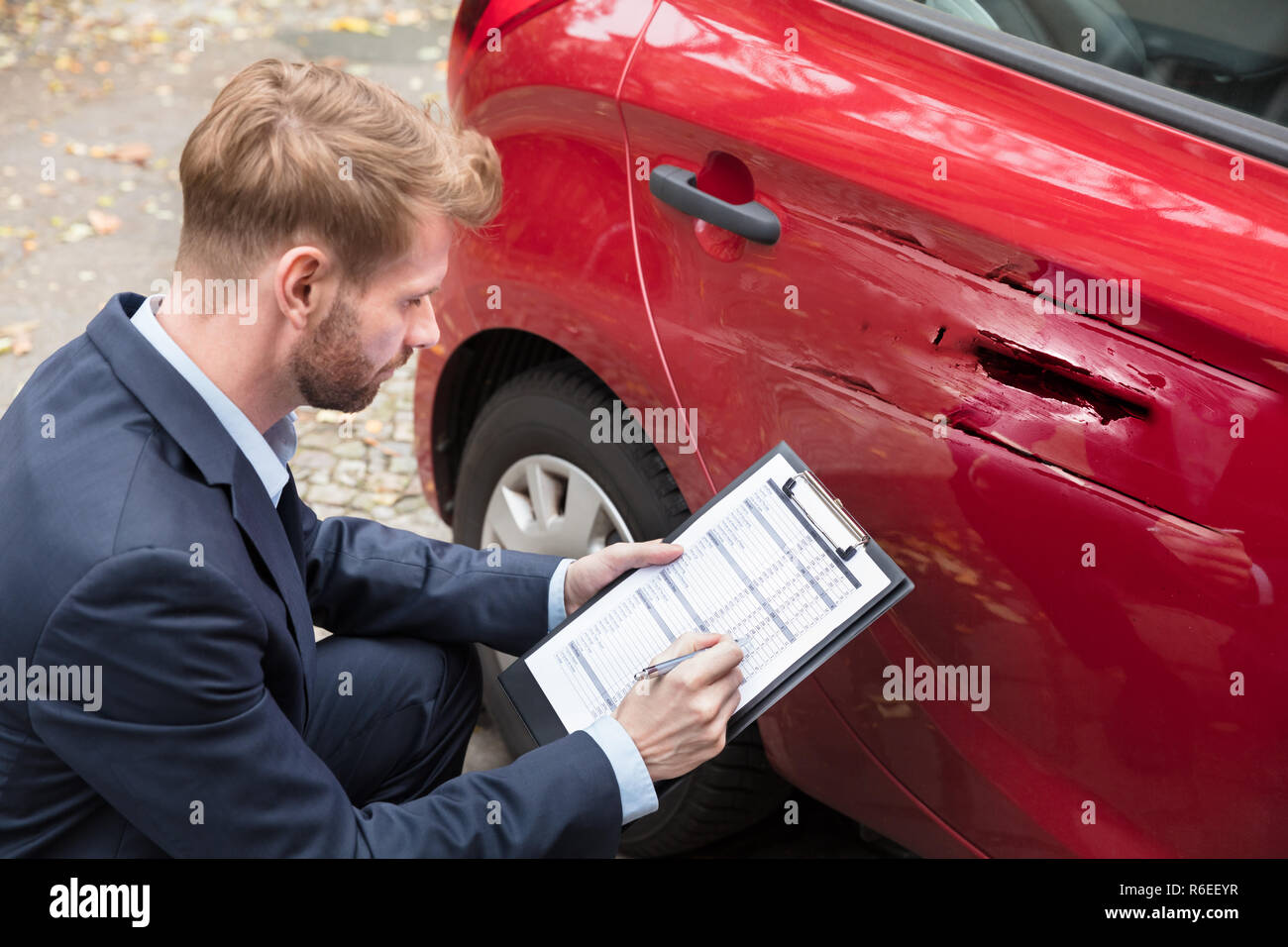 Insurance Agent Examining Car After Accident - Stock Image